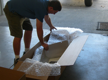 Person packing a box with bubble wrap