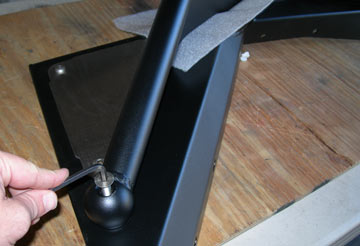 A person assembling powdercoated black arched tube fender turning a bolt