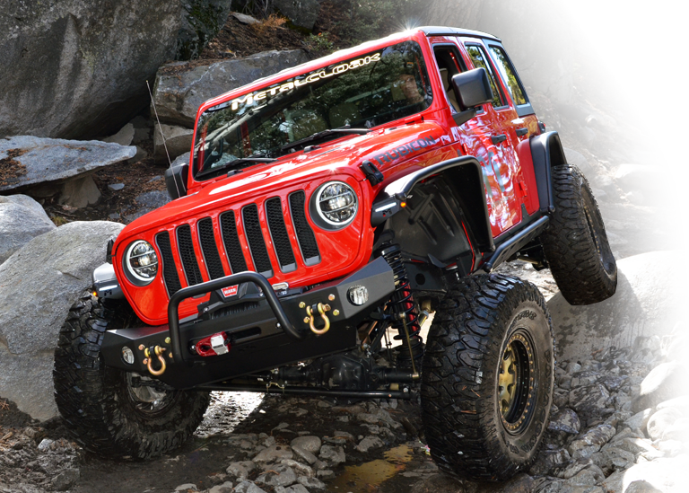 Red Jeep JL crawling over large boulders