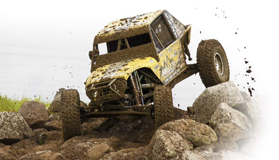 Rock crawler covered in mud racing over boulders
