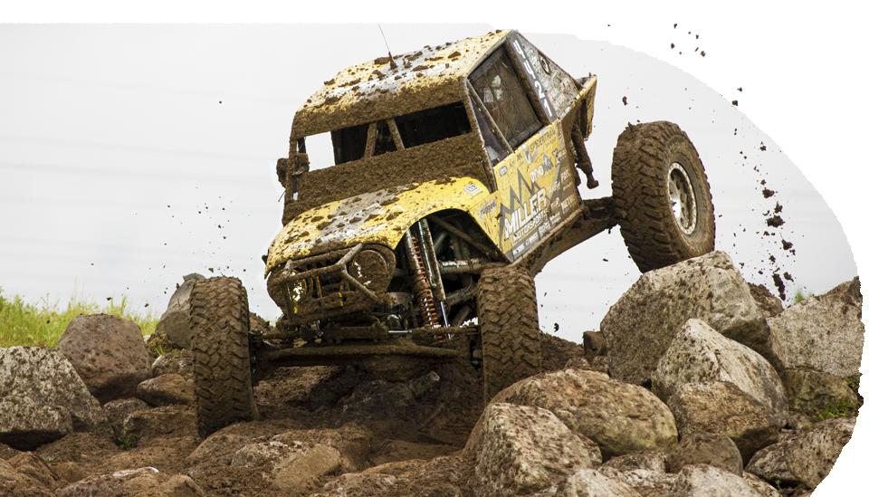 Rock crawler covered in mud racing over boulders