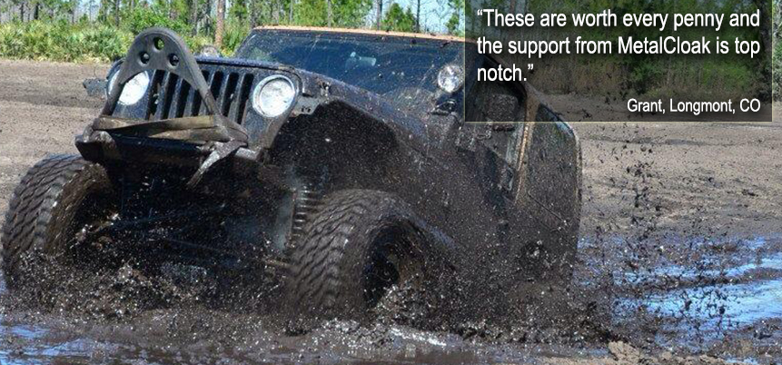 Black Jeep driving through a mud puddle