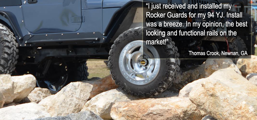 Dark gray jeep with silver rims climbing over rocks